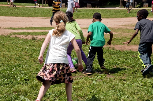 Boys and girls as they were playing ball on grass